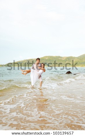 outdoor portrait of young romantic couple in white cotton clothes on beach of Phuket island, Thailand. Man holding girl on hands. - stock photo