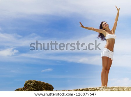 outdoor portrait of young smiling happy woman in white bikini on blue sky background - stock photo