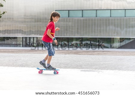outdoor portrait of young smiling teenager boy riding short modern cruiser skateboard, urban background - stock photo