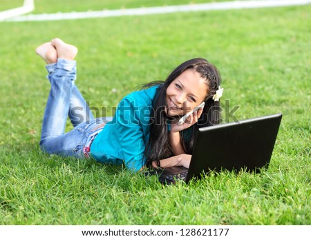 Outdoor portrait of young woman lying down using a laptop - stock photo