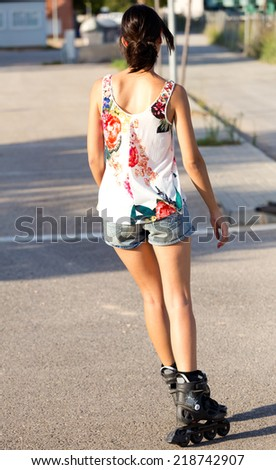 Outdoor portrait of young woman with roller skate riding in the park. - stock photo