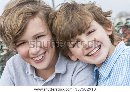 Outdoor portrait photograph of young happy boy children brothers smiling together - stock photo
