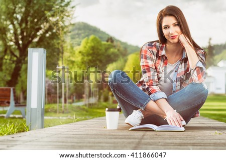 Outdoor relaxation concept with beautiful woman reading a book and enjoying coffee in the park - stock photo