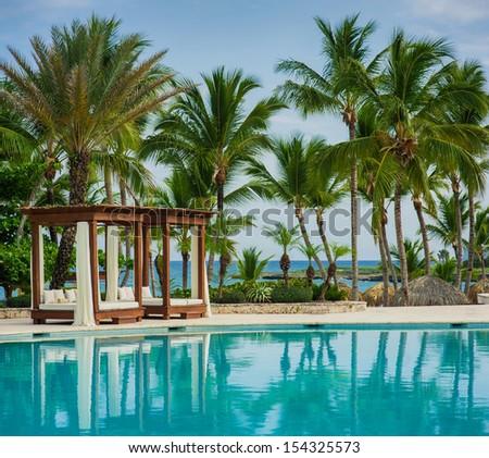 Outdoor resort pool Swimming pool of luxury hotel. Swimming pool in luxury resort near the sea. Tropical Paradise. Swimming pool in spa resort. Dominican Republic, Seychelles, Caribbean, Bahamas. - stock photo
