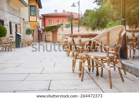 Outdoor restaurant summer terrace at sunny day - old vintage cafe with wooden table in old town. - stock photo