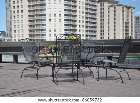 Outdoor Rooftop Urban Iron Deck Patio Furniture High Rise Buildings in the Background - stock photo