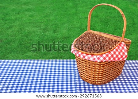 Outdoor Rustic Picnic Table  With Hamper And Blue Checkered Tablecloth On The Lawn In The Park Rest Area. Breaking Concept - stock photo