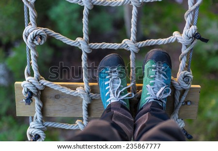 outdoor shoes on a rope grid , in an adventure park - stock photo
