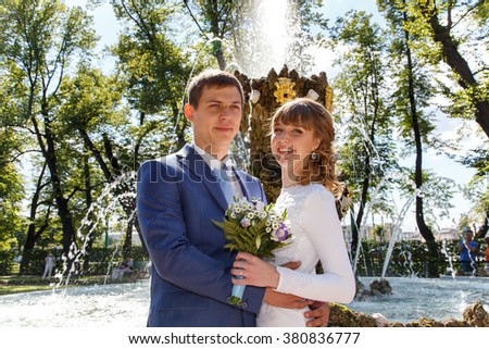 Outdoor shot of bride and groom standing near fountain in park - stock photo