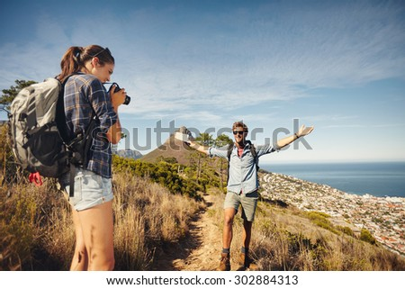 Outdoor shot of young woman photographing her boyfriend in countryside while hiking. Hiker couple enjoying during summer vacation. - stock photo
