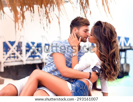 Outdoor solar fashion close-up portrait of a beautiful couple in a lively fun on a summer day in the exotic nature.Enjoying, love,experience joy.Fashion couple hugs and kissing,California beach,love - stock photo