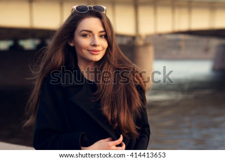 Outdoor spring or autumn portrait of young beautiful pretty woman with long hair posing in city at sunset - stock photo