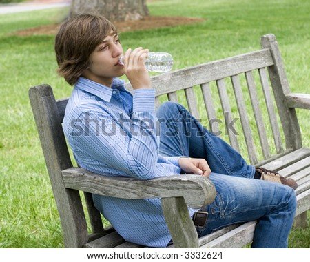 Outdoor spring portrait of a teenaged boy and a bench. - stock photo
