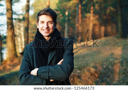 Outdoor spring portrait of young handsome man with beautiful smile. Boy posing in winter forest. - stock photo