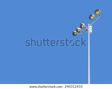 Outdoor stadium lights against daytime blue sky. Single row of bulbs on tall metal pole. Room for text, copy space. Horizontal composition.  - stock photo