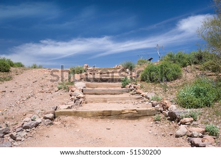 Outdoor stairs in the desert leading to a bright blue sky - stock photo