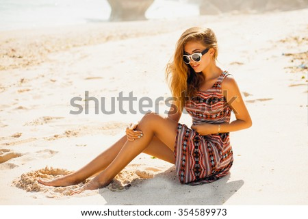 Outdoor street fashion style woman,posing with trendy sunglasses,and boho style dress,amazing beach style girl,windy hair,toned,sugaring legs,beach wear,tender skin, - stock photo