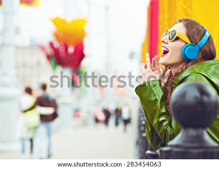 outdoor street style hipster dj woman in yellow sunglasses and dj headphones listen music and smile couples background - stock photo
