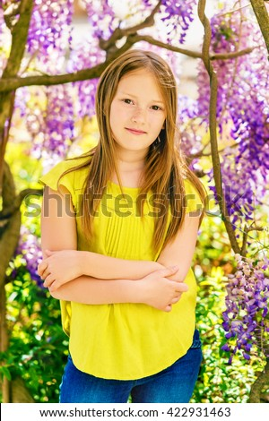 Outdoor stylish vertical portrait of a cute little girl of 8-9 years old, standing next to beautiful purple wisteria flowers, wearing green blouse, arms crossed - stock photo