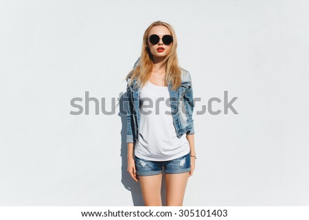 Outdoor summer fashion portrait of beautiful elegant woman wearing vintage sunglasses,retro outfit,posing at windy sunny day in summer outfit,hipster outfit..e old european city,white wall - stock photo