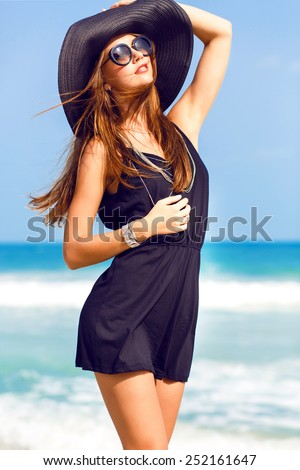 Outdoor summer fashion portrait of sexy woman in stylish elegant black clothes retro hat and sunglasses posing at tropical beach, amazing view  on clear blue ocean. - stock photo