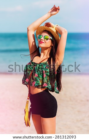Outdoor summer  lifestyle portrait of  perfect fit   smiling  woman with perfect body  having fun  on the tropical  beach wearing straw hat.    Bright colors. Happy mood.   - stock photo