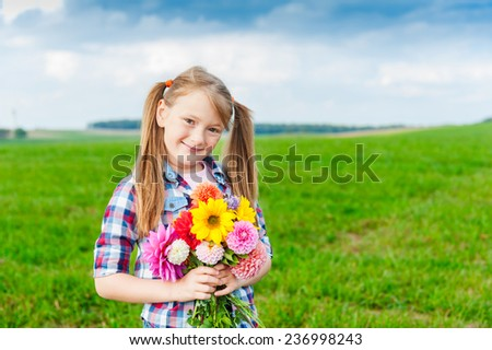 Outdoor summer portrait of adorable little girl holding bouquet of colorful flowers - stock photo