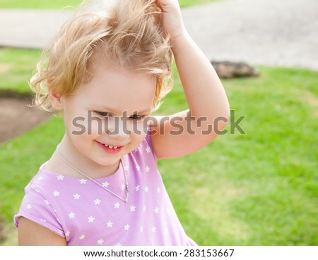 Outdoor summer portrait of cute playful smiling Caucasian blond baby girl in a park - stock photo