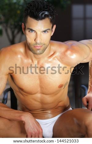 Outdoor summer portrait of sexy male model relaxing in underwear - stock photo