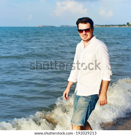 Outdoor summer portrait of smiling happy man in jeans shorts and white shirt on the beach near the sea blue sky and sun, walking and having fun on tropic island - stock photo