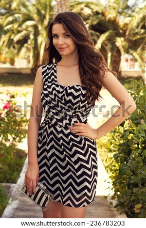 Outdoor summer portrait of young beautiful girl with long curly hair posing in short white and black stylish dress in tropical park - stock photo
