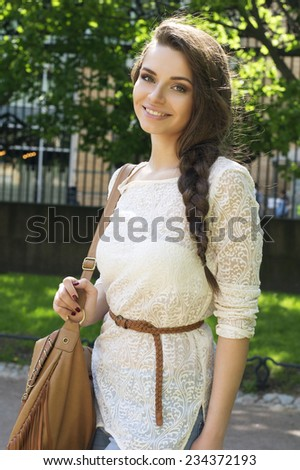 Outdoor summer portrait of young beautiful girl with stylish braid wearing fashionable white lace dress and looking at you - stock photo