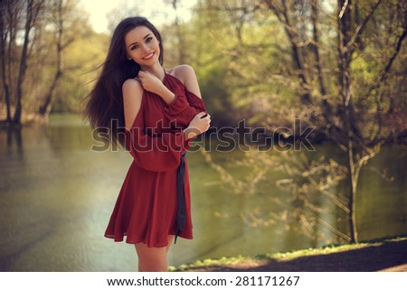 Outdoor summer portrait of young positive smiling happy girl posing in red summer dress in sunny summer park - stock photo