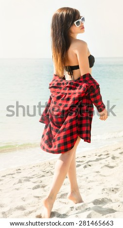 Outdoor summer stylish portrait of beautiful elegant woman with perfect fit body and long legs walking along on the beach,wear summer outfit, posing at sunny day on the  beach of sand,amazing bikini - stock photo