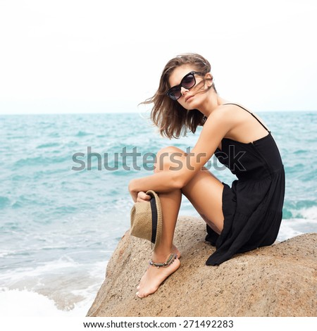 Outdoor summer sunny fashion portrait of pretty young sensual woman relaxing in black dress on the rocks and have fun alone on the ocean seashore. Outdoors lifestyle portrait - stock photo