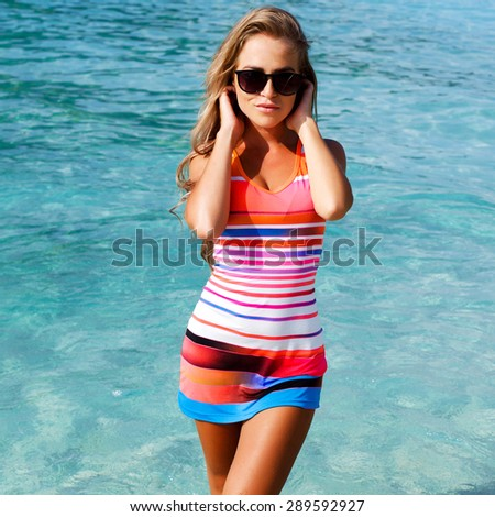 Outdoor summer vacation portrait of pretty young happy smiling blonde woman posing in red dress on blue sea background - stock photo