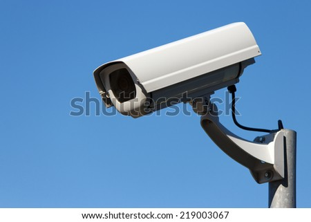 Outdoor surveillance cam and blue sky background with copy space - stock photo