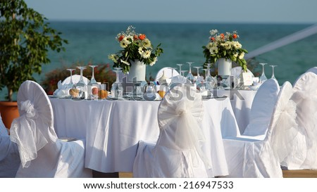 Outdoor Table Setting at Wedding Reception by the Sea. Wedding Chairs and covers at an outdoor wedding. Elegant Outdoor Wedding Table with Sea Views. Table set for an event party or wedding reception. - stock photo