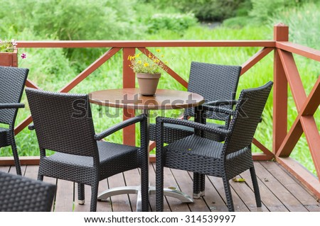 Outdoor terrace cafe table with three chairs - stock photo