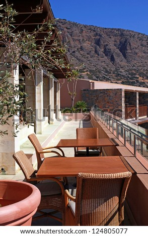 outdoor terrace with chairs and table and mountain view in a luxury resort(Crete, Greece) Vertical image - stock photo
