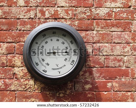 outdoor thermometer on brick wall - stock photo
