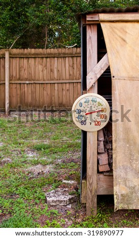 Outdoor thermometer on wood shed - stock photo