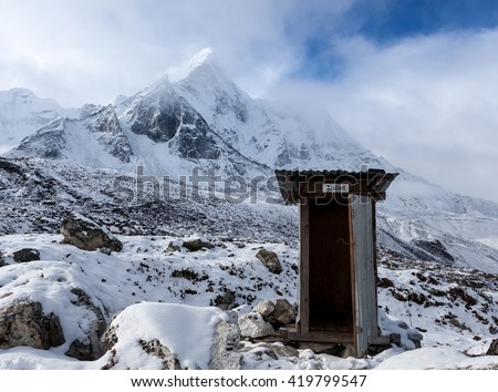 Outdoor toilet in Himalayas mountains. Unusual and funny outdoor toilet location in snowy mountains on Everest Base Camp Trek. Portal or escape from cold winter to hot summer. - stock photo