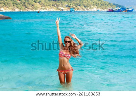 Outdoor tropic island paradise vacation beach blue sea water summer portrait of young beautiful sexy blonde woman posing have fun and get tanned stylish vivid colors photo  - stock photo