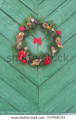 Outdoor X-mas decorative wreath is hanging on old green wooden door outside - stock photo