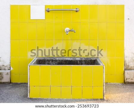 Outdoor Yellow Tiled Washbasin - stock photo
