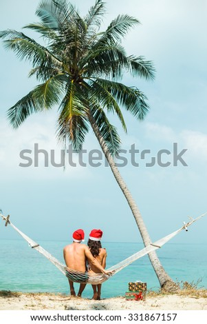 Outdoor  young couple sitting on a hammock under the palm trees celebrate new year on tropical hot countries with gifts and hugs,enjoy their holidays on hot countries,sea background,Phuket,Thailand - stock photo