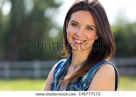 Outdoors closeup portrait of smiling cute young woman  in the park - stock photo