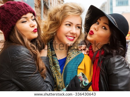 Outdoors fashion close up portrait of three young pretty smiling girls friends walking at the city. Shopping. Posing at the street. Wearing stylish outerwear and hats. Bright make up. Positive emotion - stock photo