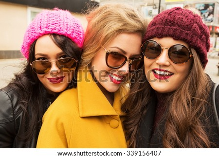 Outdoors fashion portrait of three young pretty smiling girls friends walking at the city. Shopping. Posing at the street. Wearing stylish outerwear,  hats and sunglasses. Make up. Positive. Close up - stock photo